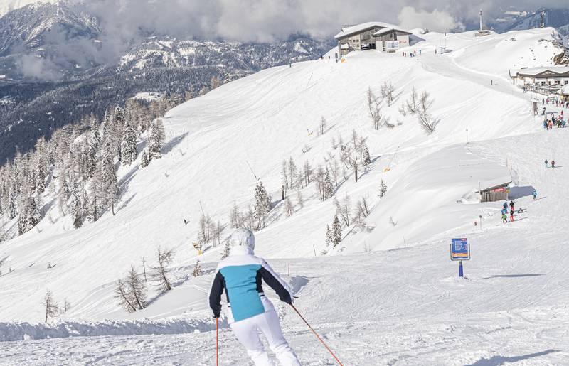 <p>Eine Skifahrerin fährt bei strahlendem Sonnenschein die frisch präparierte Skipiste hinunter. Am Horizont über dem atemberaubenden Panorama sieht man die letzten Wolken aufsteigen. Skifahren in der Region Nassfeld-Pressegger See an der italienischen Grenze in Kärnten.</p>