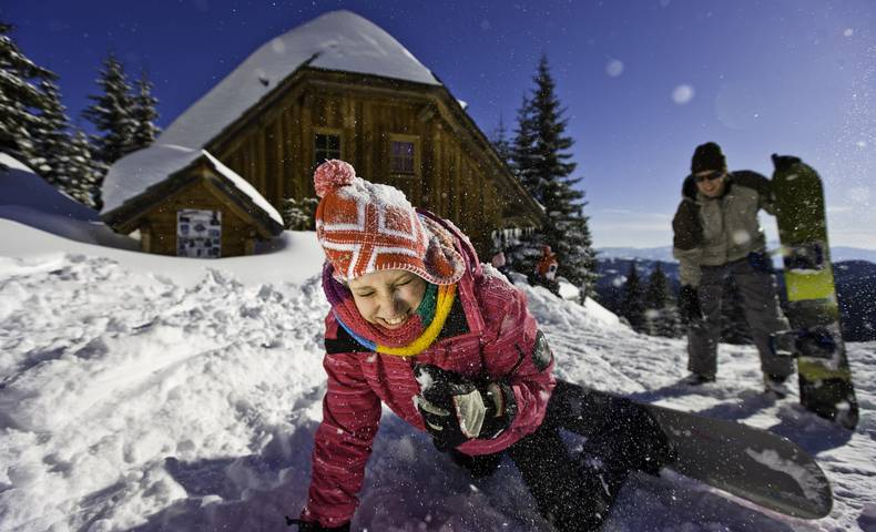 Spaß im Schnee mit dem Snowboard vor der Almhütte